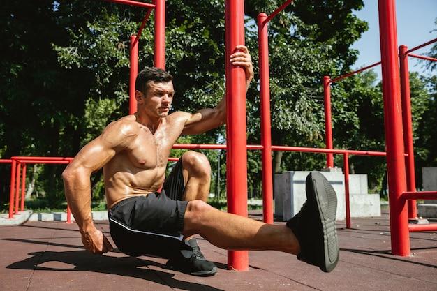 Junger muskulöser hemdloser kaukasischer mann, der kniebeugen nahe horizontalem balken tut
