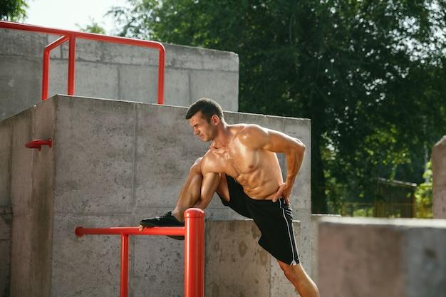 Junger muskulöser hemdloser kaukasischer mann, der streckübungen am spielplatz am sonnigen sommertag tut