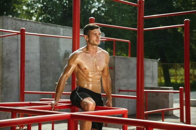 Junger muskulöser hemdloser kaukasischer mann, der streckübungen am spielplatz am sonnigen sommertag tut.