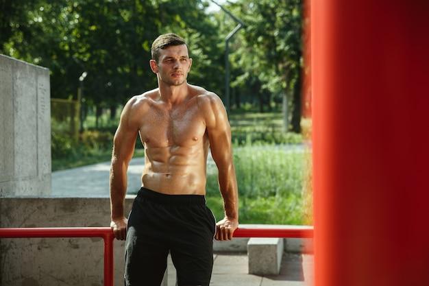 Junger muskulöser hemdloser kaukasischer mann, während er sein training auf horizontalen balken am spielplatz am sonnigen sommertag tut