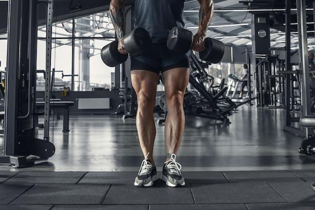 Junger muskulöser kaukasischer athlet, der im fitnessstudio mit den gewichten übt.