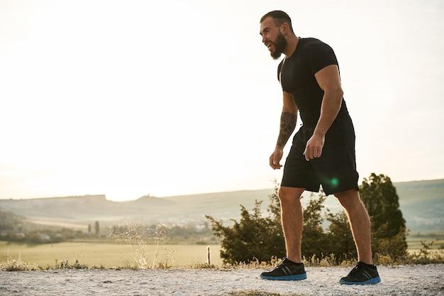 Junger muskulöser männlicher athlet, der den hügel hinauf läuft