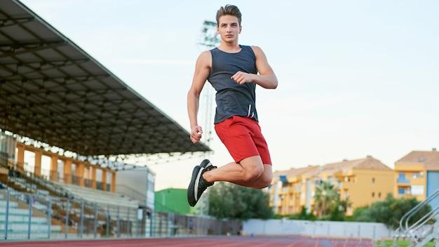 Junger muskulöser mann, der auf das stadion springt