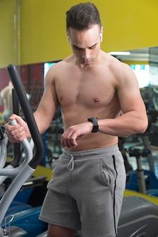 Junger muskulöser mann, der die uhr in der elliptischen maschine beobachtet.
