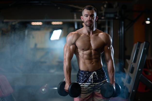 Junger muskulöser mann, der in der hand mit dummköpfen an der turnhalle aufwirft