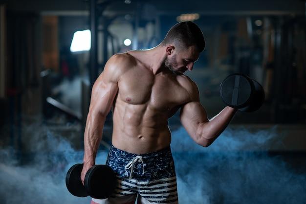 Junger muskulöser mann, der mit dummköpfen trainiert