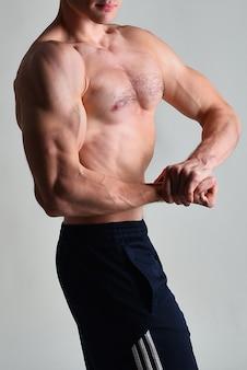 Junger muskulöser mann, der seine muskeln biegt