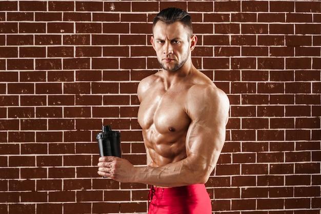 Junger muskulöser mann, der seinen perfekten körper und schüttel-apparat zeigt