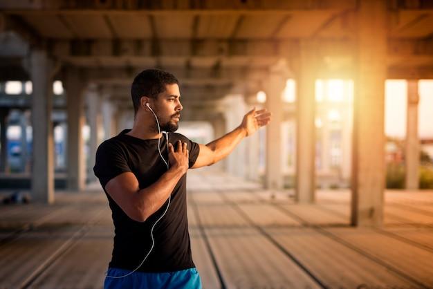 Junger muskulöser mann, der sich ausdehnt und sich auf fitness-training vorbereitet