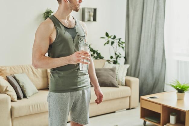 Junger muskulöser mann in der sportbekleidung, die flasche wasser durch seine brust hält, während pause zwischen sätzen des trainings in der häuslichen umgebung hat