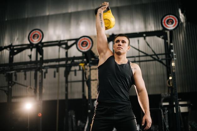 Junger muskulöser mann mit perfektem, schönem körper, der sportkleidung trägt, die schwere freie gewichte hebt