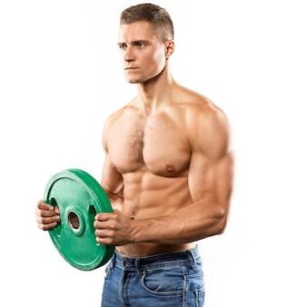 Junger muskulöser mann posiert mit langhantel-hantelscheibe auf weißer wand