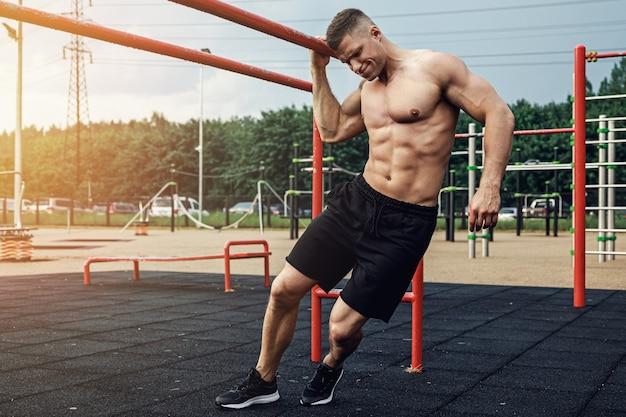 Junger muskulöser mann während seines trainings auf der straße