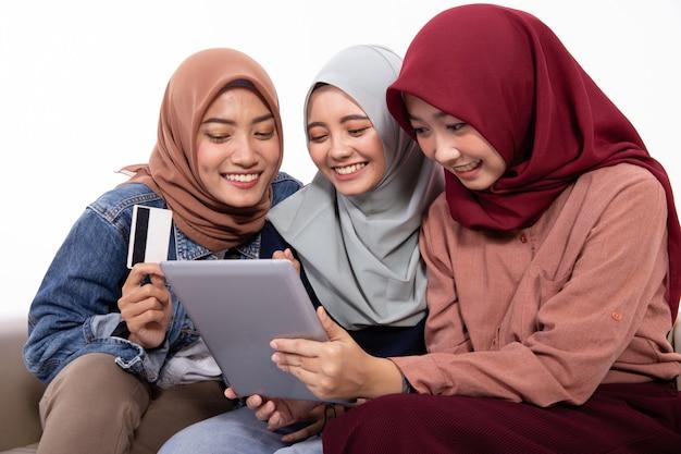 Junger muslimischer freund, der kreditkarte und tablette benutzt