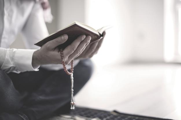 Junger muslimischer mann, der koran liest, drinnen