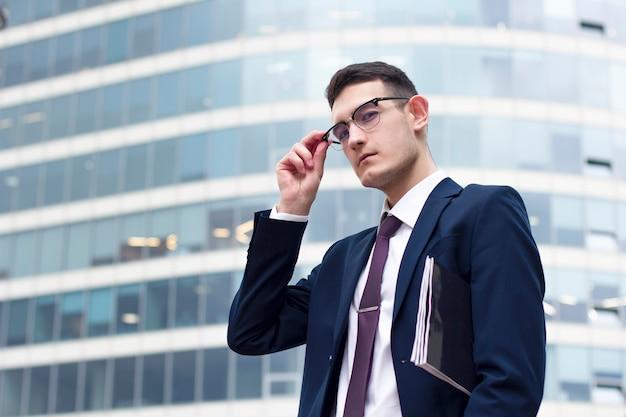 Junger mutiger überzeugter geschäftsmann, der kamera mit den zeitschriften, seine gläser halten, erfolgreicher formal gekleideter kerl im anzug mit der bindung steht im freien nahe modernem gebäude oder geschäftszentrum des büros betrachtet
