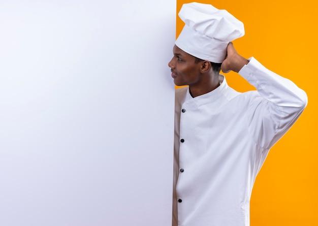 Junger nachdenklicher afroamerikanischer koch in der kochuniform steht hinter weißer wand und betrachtet wand lokalisiert auf orange wand