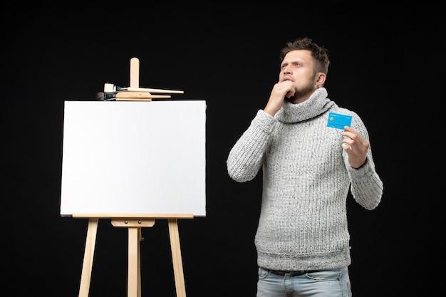 Junger nachdenklicher bärtiger künstler, der bankkarte auf isolierter schwarzer wand hält