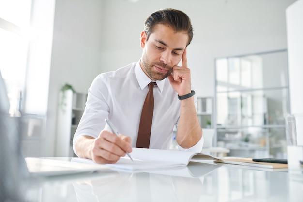 Junger nachdenklicher büroleiter, der durch schreibtisch sitzt und seite des heftes betrachtet, während plan des berichts macht
