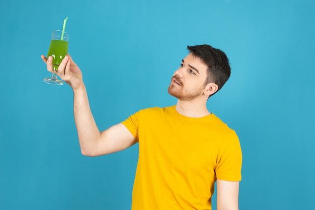 Junger nachdenklicher mann, der frischen cocktail hält und ihn auf einem blau betrachtet.