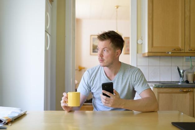 Junger nachdenklicher mann, der telefon benutzt und kaffee durch den wind trinkt