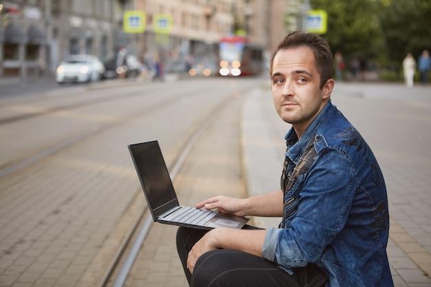 Junger nachdenklicher mann mit notizbuch in den händen sitzt nahe eisenbahnschiene auf hintergrund der reitenden straßenbahn.