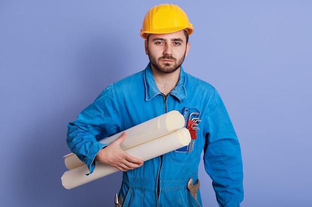 Junger nachdenklicher vorarbeiter, der blaue uniform und gelben helm hält plan des neuen projekts in händen trägt, posiert mit blaupausen, die über studiohintergrund isoliert werden, bärtiger architekt, der arbeitet, sieht ernst aus.
