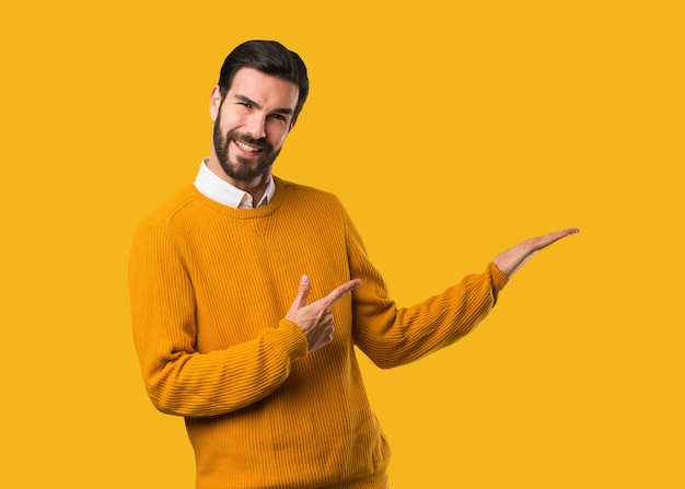 Junger natürlicher mann, der etwas mit der hand hält