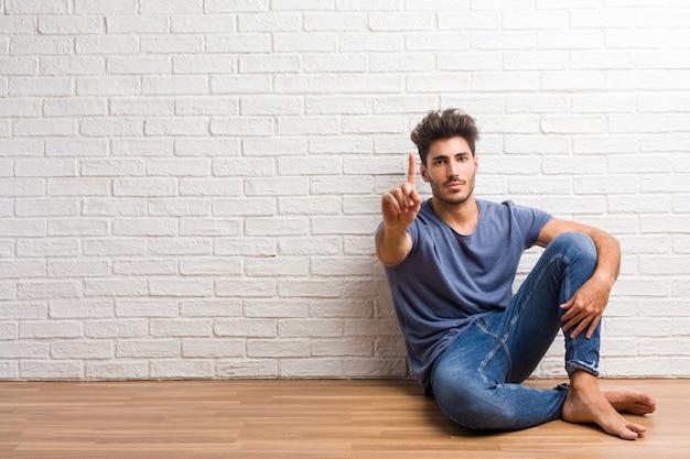 Junger natürlicher mann sitzen auf einem bretterboden, der nummer eins, symbol der zählung zeigt