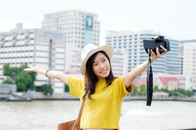 Junger netter asiatischer frauenreisender in der zufälligen art, die draußen kamera selfie im hintergrund der städtischen stadt macht