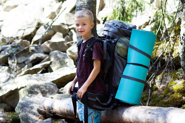 Junger netter glücklicher kinderjunge mit großem touristischem rucksack auf sonnigem felsenhintergrund