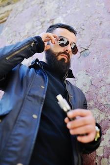 Junger netter junger kerl mit elektronischer zigarette