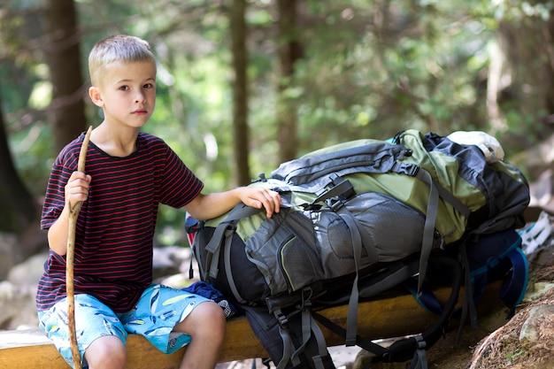 Junger netter kinderjunge mit dem stock, der allein am großen touristischen rucksack sitzt