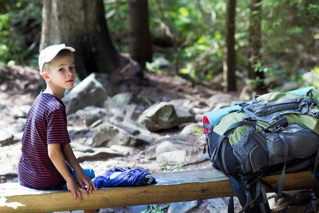 Junger netter kinderjunge mit dem stock, der allein an großem touristischem rucksack o sitzt
