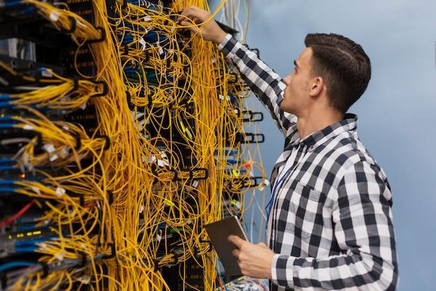Junger netzingenieur, der in einem serverraum arbeitet
