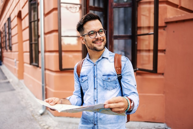 Junger niedlicher hipster, der in einer alten stadt steht, karte hält und die ansicht genießt.