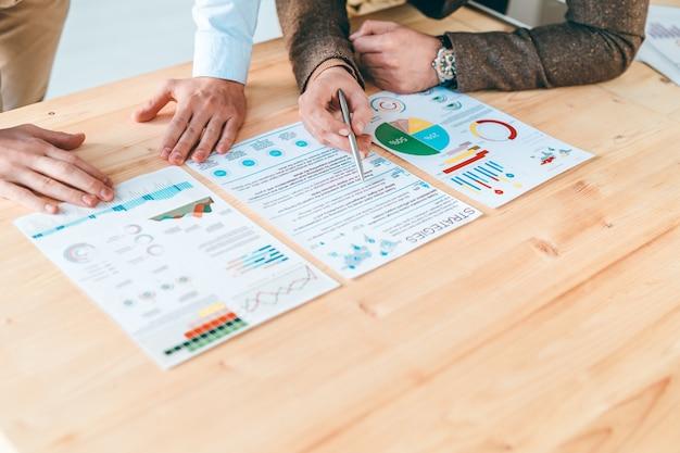 Junger ökonom mit stift, der auf finanzinformationen im dokument zeigt, während geschäftsstrategien mit kollegen bespricht