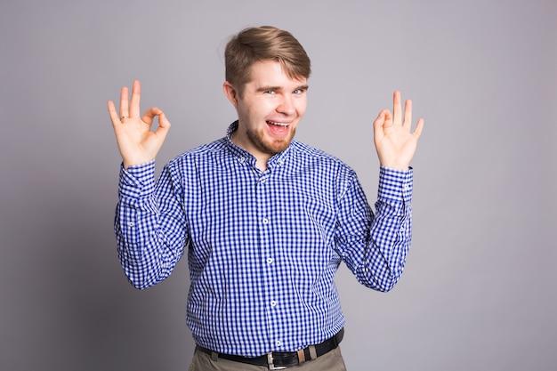Junger optimistischer mann auf grauer wand zeigt ok mit positiven emotionen des inhalts und des glücks