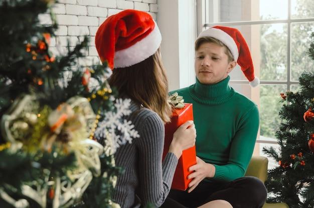Junger paarmann mit rotem sankt-hut überraschend und der freundin mit weihnachten weihnachtsgeschenkbox gebend, das im haus feiert