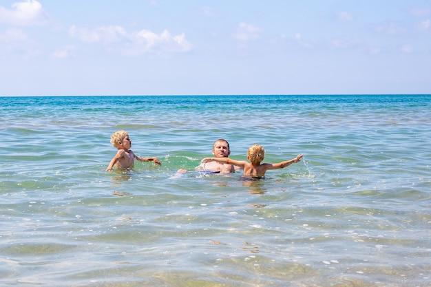 Junger papa mit blonden jungs schwimmt im meer. schöne sommerferien.