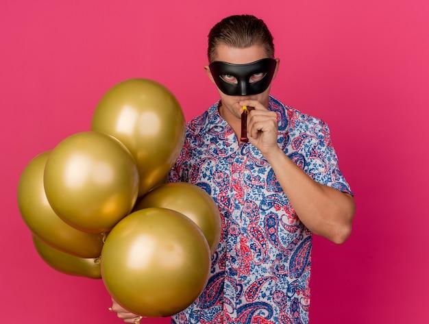 Junger partei-typ, der maskerade-augenmaske hält, die luftballons hält und partygebläse auf rosa lokalisiert bläst