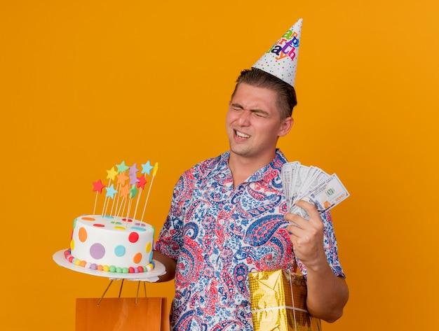 Junger party-typ, der geburtstagskappe mit geschlossenen augen trägt, die geschenke mit kuchen und bargeld lokalisiert auf orange hält