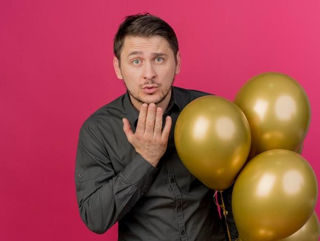 Junger party-typ, der schwarzes hemd trägt, das nahe luftballons steht, die kussgeste lokalisiert auf rosa zeigen