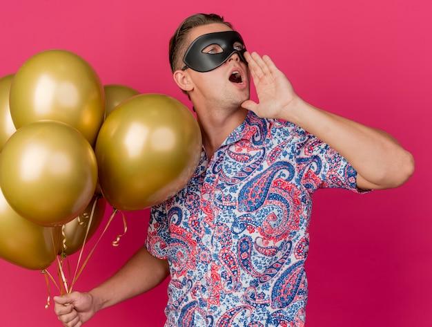 Junger party-typ, der seite sieht, die maskerade-augenmaske trägt, die luftballons hält und jemanden lokalisiert auf rosa anruft
