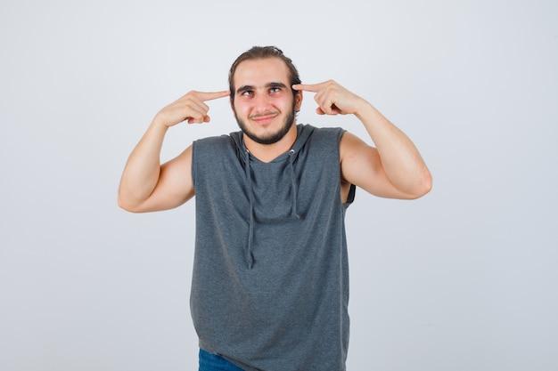 Junger passender mann, der auf blinzelnde augen im ärmellosen kapuzenpulli zeigt und fröhlich, vorderansicht schaut.