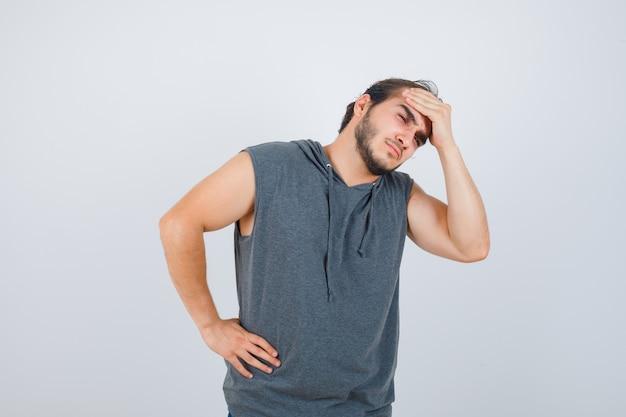 Junger passender mann, der hand auf stirn in ärmellosem kapuzenpulli hält und schmerzhafte vorderansicht schaut.