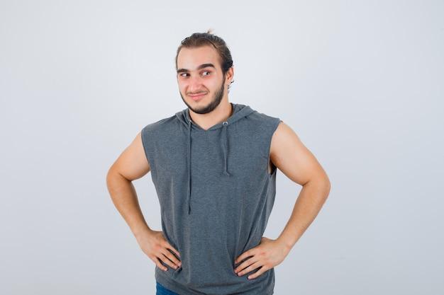 Junger passender mann, der mit den händen an der taille im ärmellosen kapuzenpulli aufwirft und fröhlich aussieht. vorderansicht.