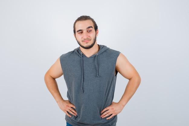Junger passender mann, der mit den händen an der taille im ärmellosen kapuzenpulli aufwirft und glückselig aussieht. vorderansicht.
