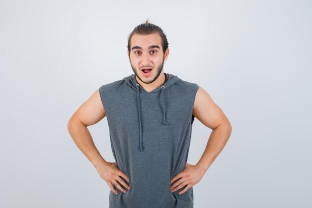 Junger passender mann, der mit den händen an der taille im ärmellosen kapuzenpulli aufwirft und schockiert schaut, vorderansicht.