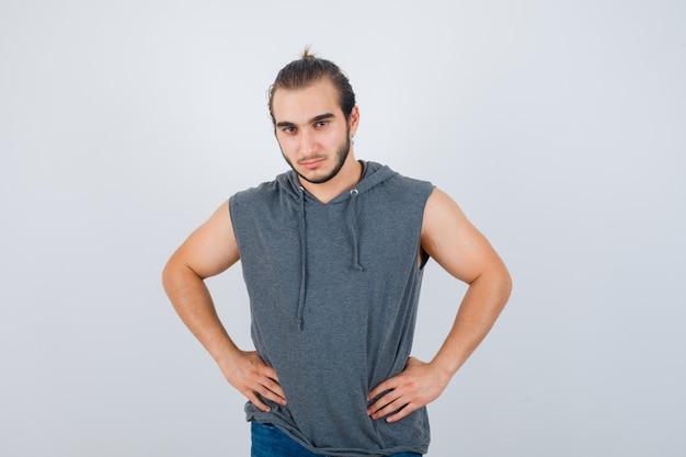 Junger passender mann, der mit den händen an der taille im ärmellosen kapuzenpulli aufwirft und selbstbewusst aussieht, vorderansicht.